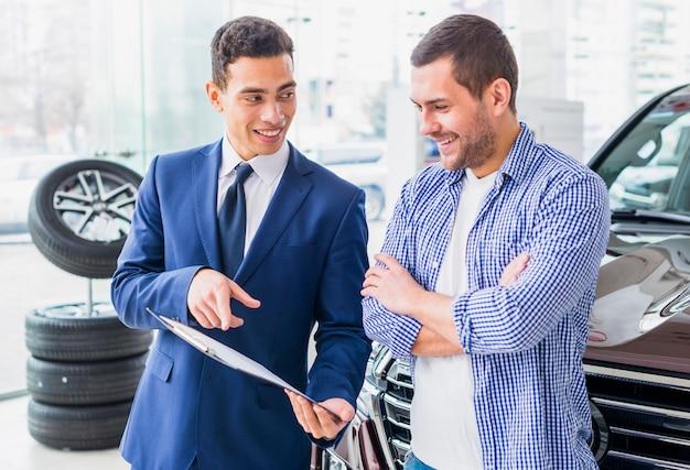 Negociante de carro falando ao cliente