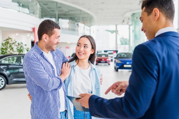 Negociante de carro falando com clientes