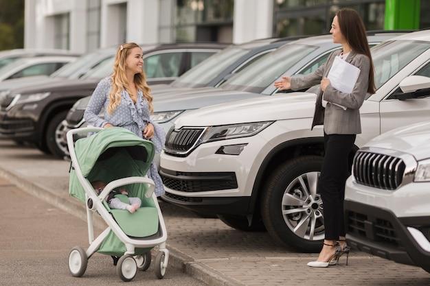 Negociante de carro fêmea que dá boas-vindas a um comprador