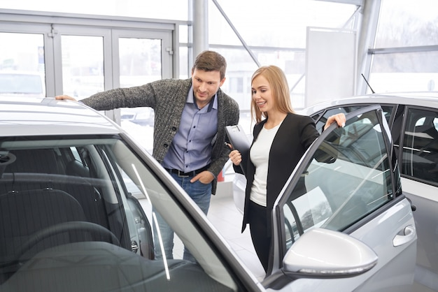 Negociante de carro fêmea que mostra o automóvel ao comprador potencial.