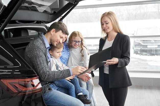 Negociante de carro feminino, assinando contrato com o cliente no salão do automóvel