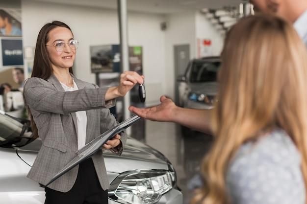 Negociante de carro feminino oferecendo chaves