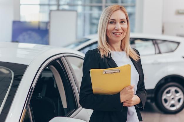 Negociante de carro profissional posando no salão do automóvel, sorrindo para a câmera