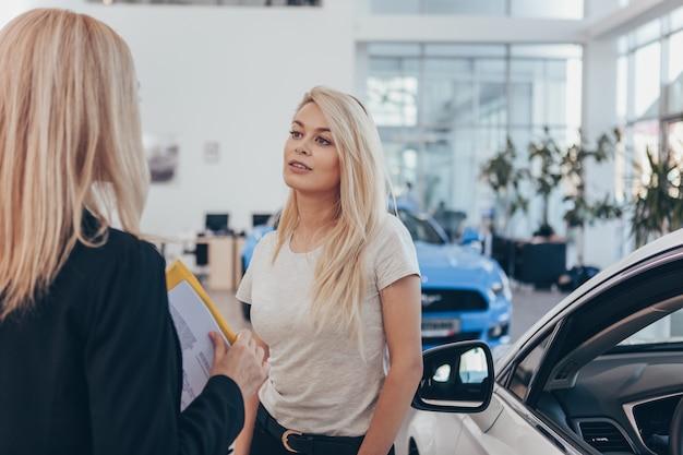 Negociante de carro profissional que ajuda seu cliente a escolher o automóvel novo