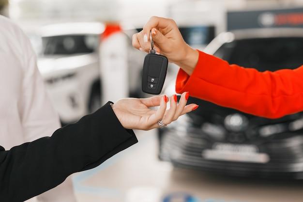 Negociante de carro que dá a chave para a mulher. mãos femininas closeup.