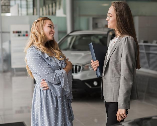 Negociante de carro que fala com mulher bonita