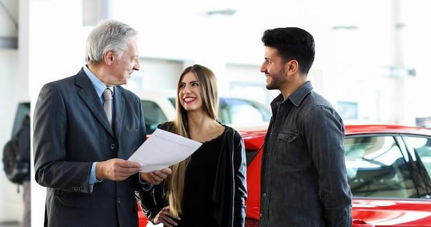 Negociante de carro que lê um contrato a um par em um auto showroom