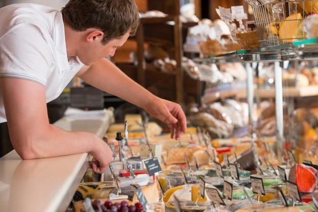 Negociante trabalhando em uma caixa de vidro de queijo em uma mercearia