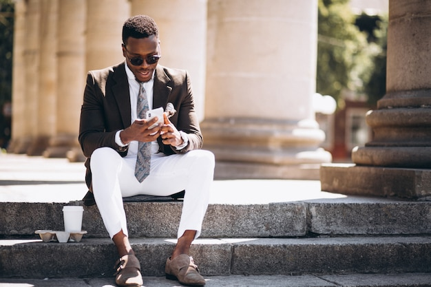 Negócio americano africano com café e telefone sentado nas escadas de um edifício