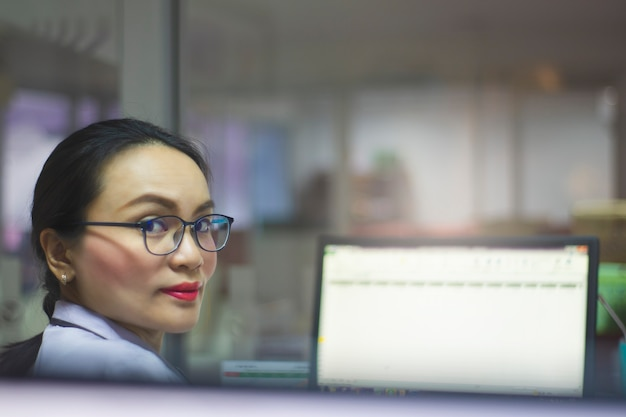 Negócio asiático da carreira da mulher e computador ou tabuleta de trabalho no escritório no fundo branco.