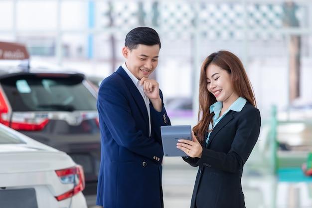 Negócio asiático do homem de negócio que compra o carro brandnew
