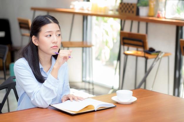 Negócio bonito mulher asiática pensando idéia e escrevendo no notebook