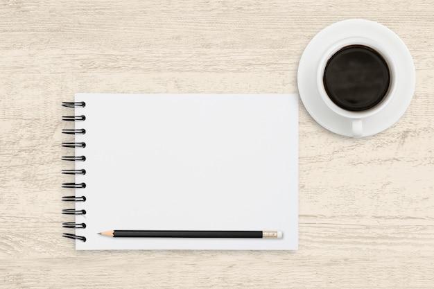 Negócio da vista superior da folha do caderno do livro branco com a xícara de café no fundo de madeira.