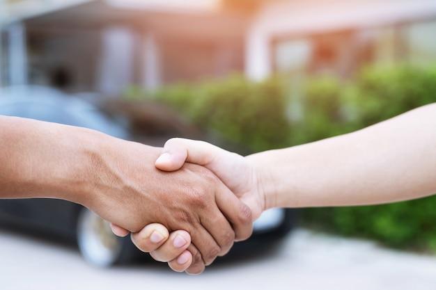 Negócio de automóveis. perto de um negociante de homem de negócios oferece o carro ao novo proprietário e aperta a mão entre dois parabéns aos clientes.
