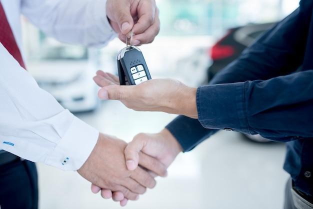 Negócio de automóveis, venda de carros, acordo, gesto e conceito de pessoas - close-up de revendedor, dando a chave ao novo proprietário e apertando as mãos no salão do automóvel ou salão de beleza