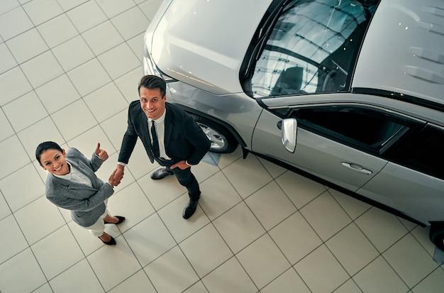 Negócio de automóveis, venda de carros, negócio, gesto e conceito de pessoas - vista superior do revendedor e novo proprietário apertando as mãos em salão de automóveis ou salão.