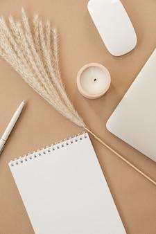 Negócio de chefe de senhora flatlay, conceito de trabalho. espaço de trabalho mínimo de mesa de escritório em casa em fundo bege pastel. caderno de folha em branco, laptop, ramo de grama de pampas, decorações.