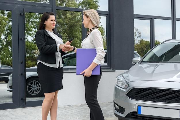 Negócio de compra de carro. duas lindas mulheres apertando a mão perto de um carro novo do lado de fora e sorrindo