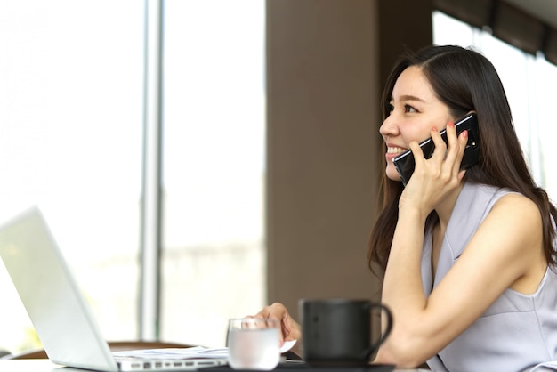 Negócio de fala da menina bonita esperta asiática no telefone celular que senta-se na cafetaria.