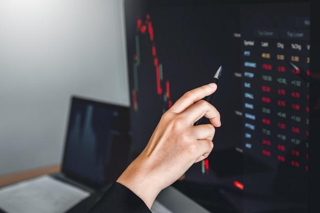 Negócio de mulher lidar investimento do mercado de ações, discutindo a negociação do mercado de ações do gráfico comerciantes de ações