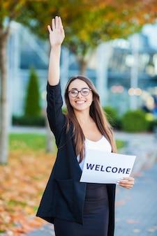 Negócio de mulheres com o cartaz com mensagem de boas vindas