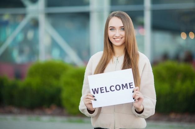 Negócio de mulheres com o cartaz com mensagem de boas-vindas