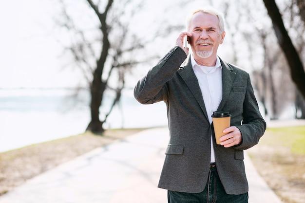 Negócio de negócios. homem de negócios sênior otimista tomando café no parque e falando ao telefone