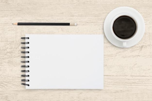 Negócio de vista superior da folha de papel branco de caderno com uma xícara de café na mesa de madeira.
