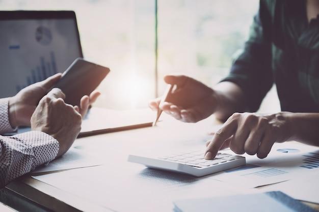 Negócio e parceria que discutem usando a calculadora para rever o anuário do balanço patrimonial com pena de terra arrendada e usar o laptop ao orçamento calculador. integridade de auditoria antes do conceito de investimento.