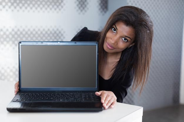 Negócio jovem atraente na suite forte preta sentar na mesa de escritório