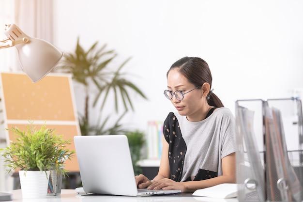 Negócio, mulher asian, triste, e, preocupado, trabalhando, com, um, laptop, em, um, escritório