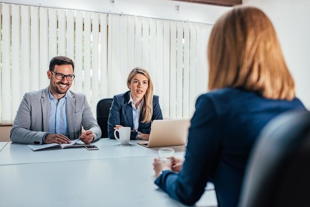 Negócio - mulher nova que senta-se na entrevista de trabalho.