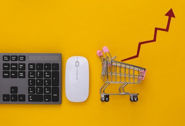 Negócio online. teclado de pc e carrinho de compras com seta de crescimento em amarelo