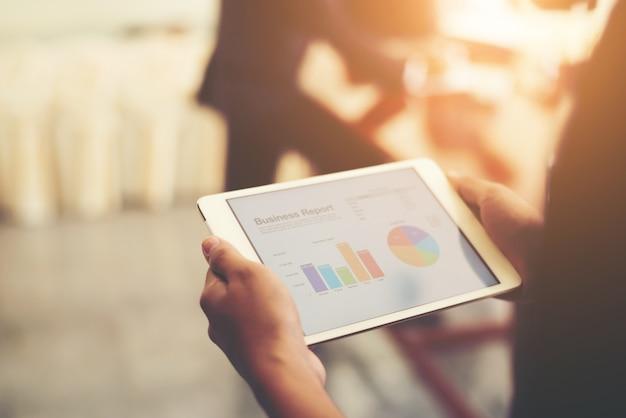 Negócio pessoa mão segurando estatísticas financeiras exibido em t
