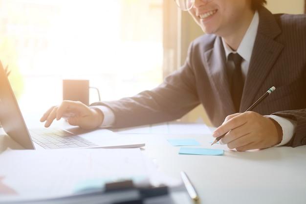 Negócio que trabalha com laptop e sorriso na foto do tiro do close up da cara. Foto Premium
