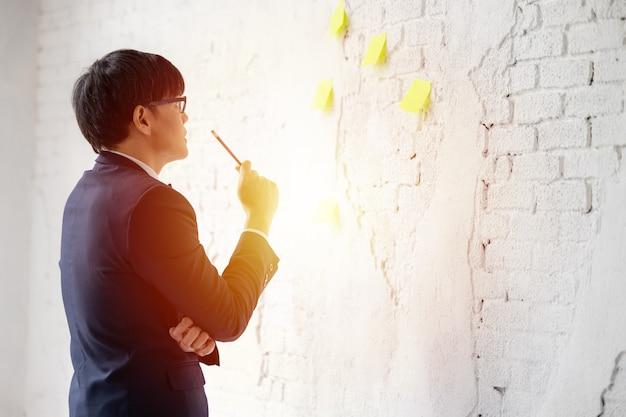 Negócios asiáticos em óculos fica na janela usar cronograma de lembrete de papel notas auto-adesivas para discutir a ideia no escritório, empresário olhando e pensando bloco de notas na parede branca.