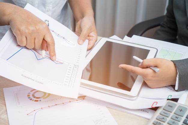 Negócios asiáticos trabalhando e estudando juntos discutir finanças com tablet gráfico do documento pa
