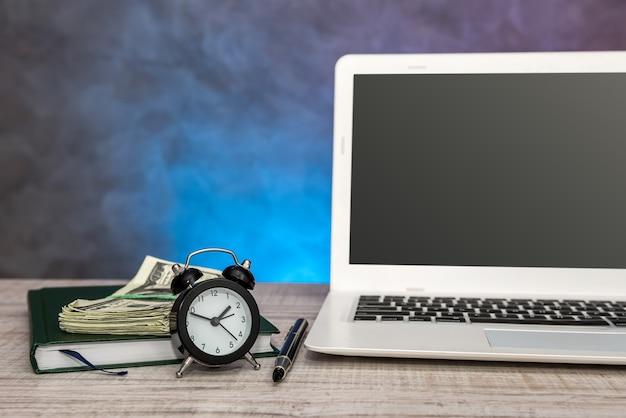 Negócios - chave do carro, dinheiro do laptop e bloco de notas na mesa.