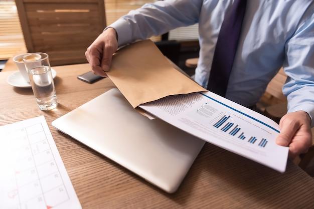 Negócios. close-up de documentos de negócios com gráficos e dados estatísticos sendo retirados do envelope por um gerente homem responsável e trabalhador
