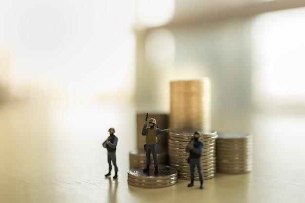 Negócios, conceito de segurança financeira. close-up do grupo de figura em miniatura de soldado em pé e guarda com pilha de moedas
