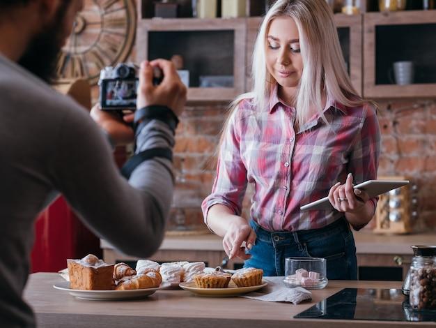 Negócios de blogs de comida. estilo de vida de casal. homem atirando em mulher apontando para o bolinho. variedade de doces ao redor.