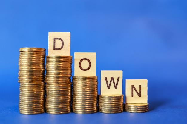 Negócios, dinheiro e conceito financeiro. close-up da letra em inglês para baixo do bloco de madeira em cima da pilha de moedas de ouro sobre fundo azul.