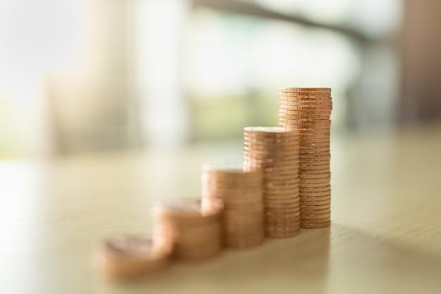 Negócios, dinheiro, finanças, segurança e conceito de economia. close-up da pilha de moedas na mesa de madeira sob a luz solar