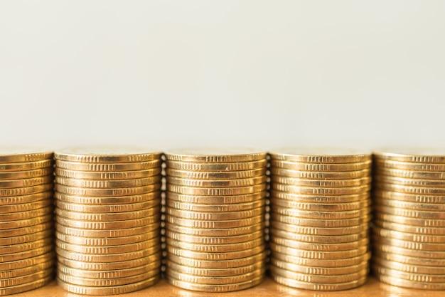 Negócios, dinheiro, finanças, segurança e conceito de economia. feche acima de cinco pilhas de moedas de ouro na tabela de madeira com cópia sapce.