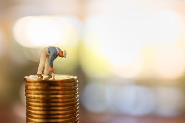Negócios, dinheiro, planejamento e conceito de economia. feche acima da limpeza e da pintura do trabalhador sobre a pilha de moeda de ouro com espaço da cópia.