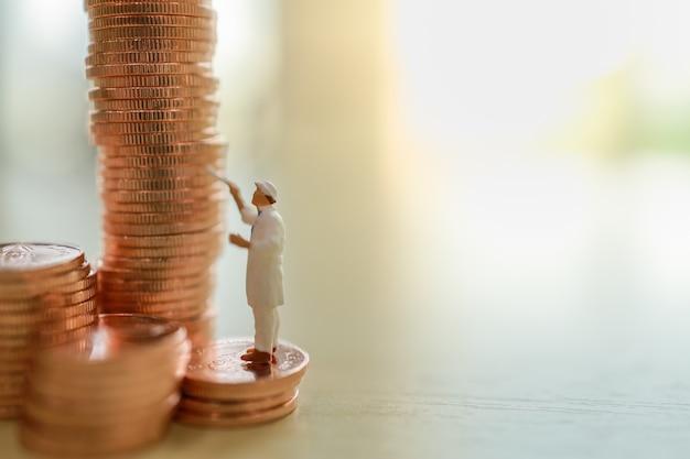 Negócios, dinheiro, planejamento e conceito de economia. feche acima da pilha da pintura do trabalhador de moedas na tabela de madeira com espaço da cópia.