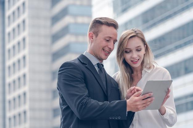 Negócios discutem sobre trabalho e bolsa de valores e tablet na cidade