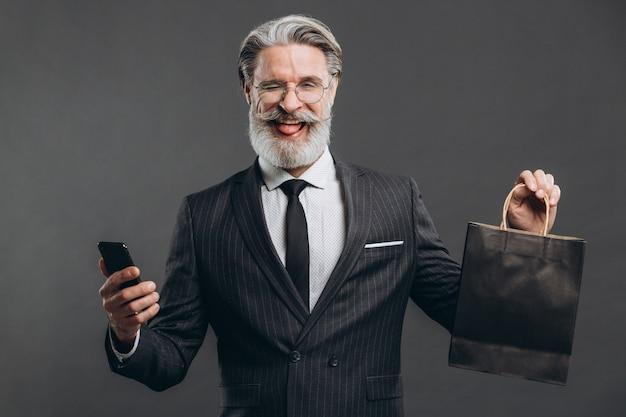 Negócios e elegante homem maduro barbudo em um terno cinza com pacote preto fazendo compras e mostrando a língua.