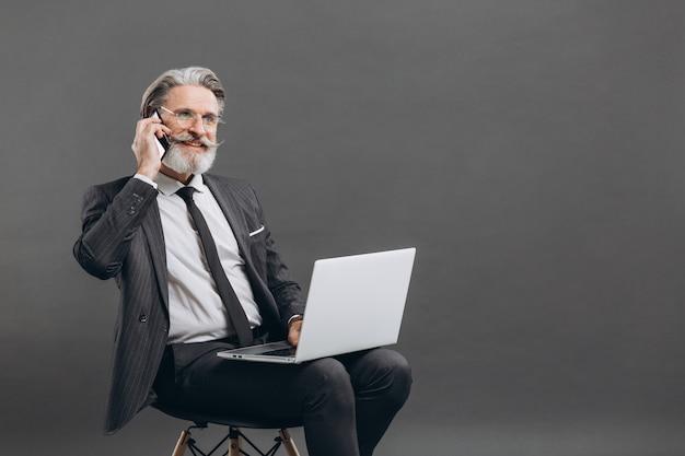 Negócios e elegante homem maduro barbudo em um terno cinza, levando por telefone e usando o laptop na parede cinza.