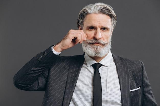 Negócios e elegante homem maduro barbudo em um terno cinza, segurando o bigode na parede cinza.